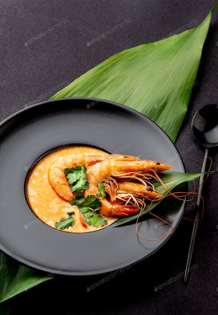 Meeresfrüchtesuppe mit ganzen Garnelen und tropischen Blättern auf schwarzem Teller, schwarzem Hintergrund dekoriert.