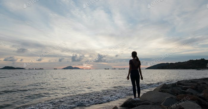 Woman do yoga and stand beside the beach