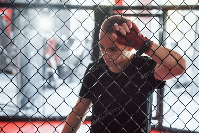 Taking a break. Sportsman at boxing ring have exercise. Leaning on the fence
