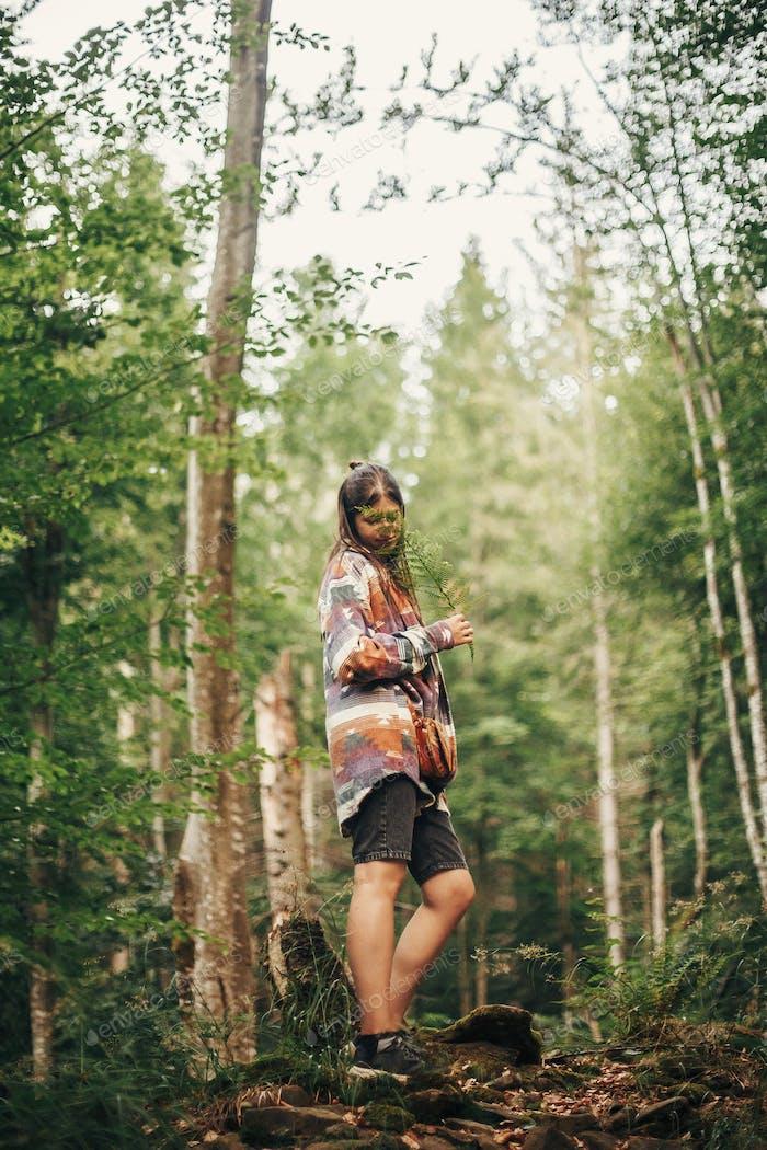 chica viajera con estilo caminando en el bosque soleado y las montañas