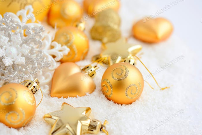 Christmas gold ornaments on the snow. Festive Christmas backgrou