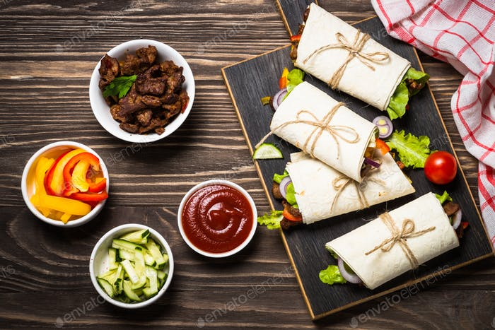 Burritos tortilla wraps with beef and vegetables top view