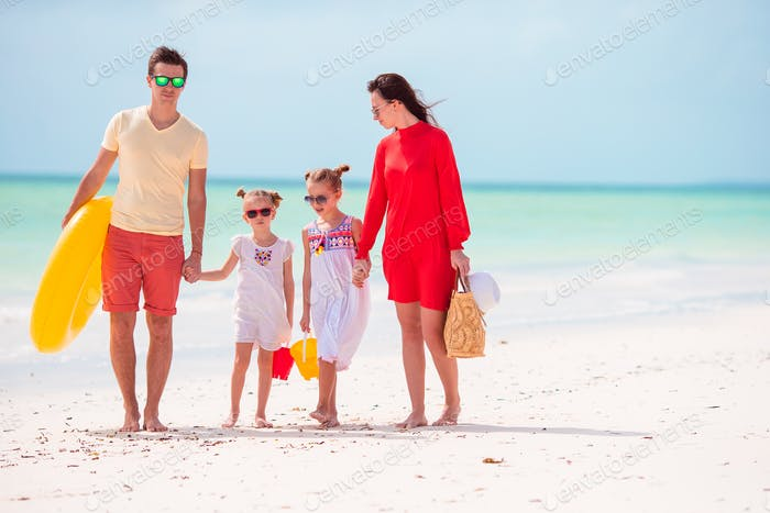 Family of four on beach vacation with inflatable ring and toy buckets
