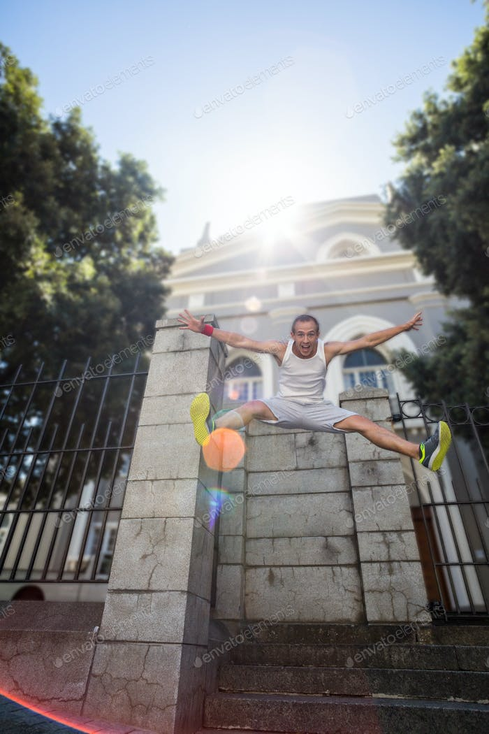 Extreme athlete jumping in the air in front of a building in the city