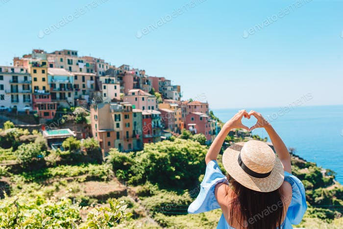 Happy girl making with hands heart shape on the old coastal village in Cinque Terre National Park