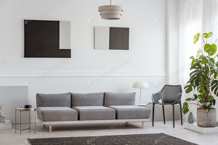 Trendy living room interior with white wall, painting and grey settee