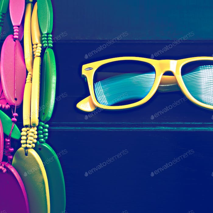 Glasses and brightly colored beads on black grungy background