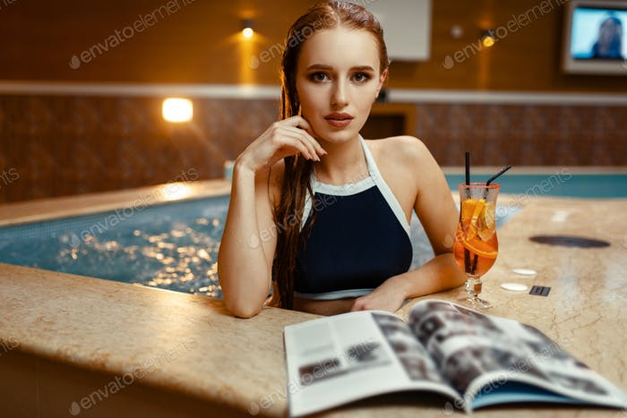 Lady with cocktail and journal at the pool side