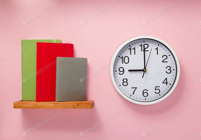 notepad and clock on shelf at wall background