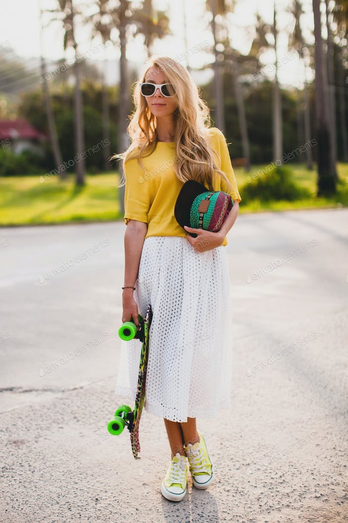 hipster cool woman with skate board and cap posing smiling on vacation