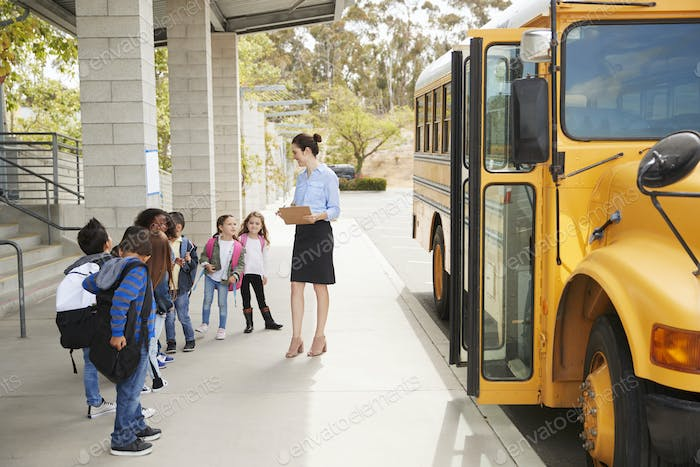 Teacher talks to young school kids by school bus, side view