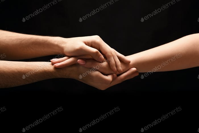 Hands of man and woman in love, isolated on black