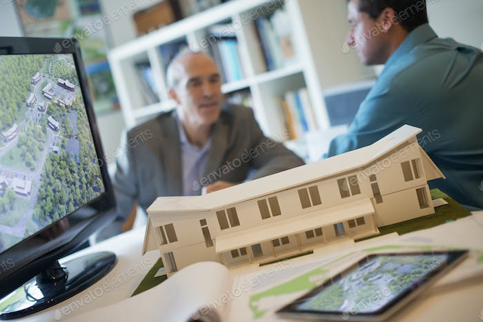 Architects working on a construction project, scale model in foreground.