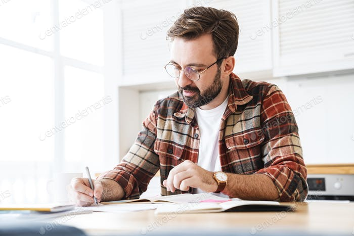 Portrait of young bearded man working with notes at home