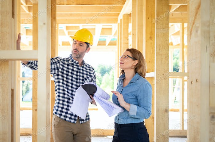 Architect or engineer with blueprints meeting with owner of building house on construction site