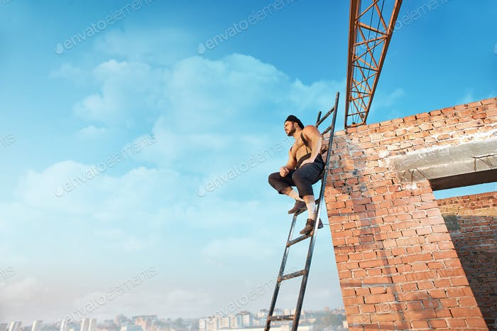 Builder with bare torso sitting on ladder