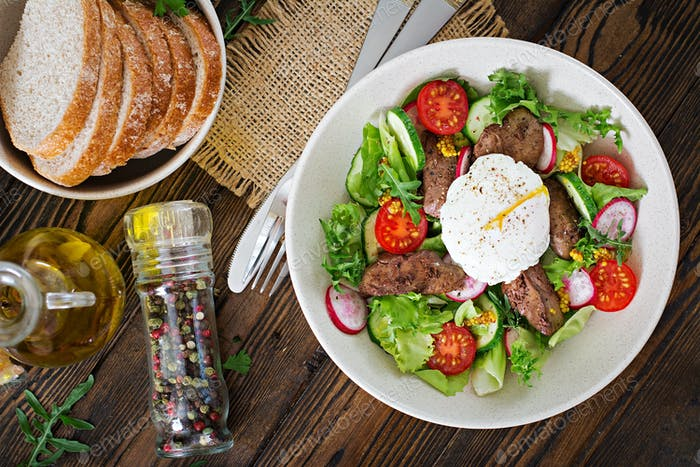 Warm salad from chicken liver, radish, cucumber, tomato and egg poached.