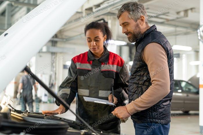 Técnica joven del servicio de reparación de automóviles mirando el compartimiento del motor abierto