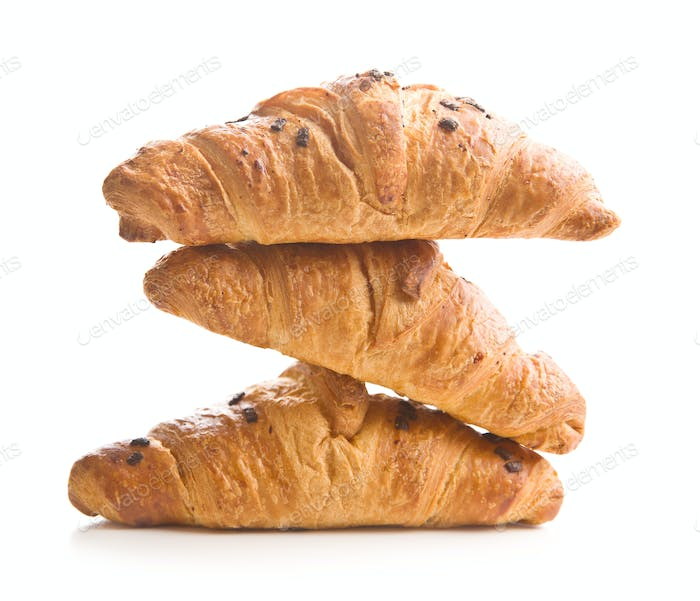 Three croissants with chocolate crumbs.