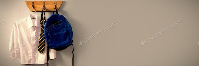Schuluniform und Schulranzen hängen am Haken