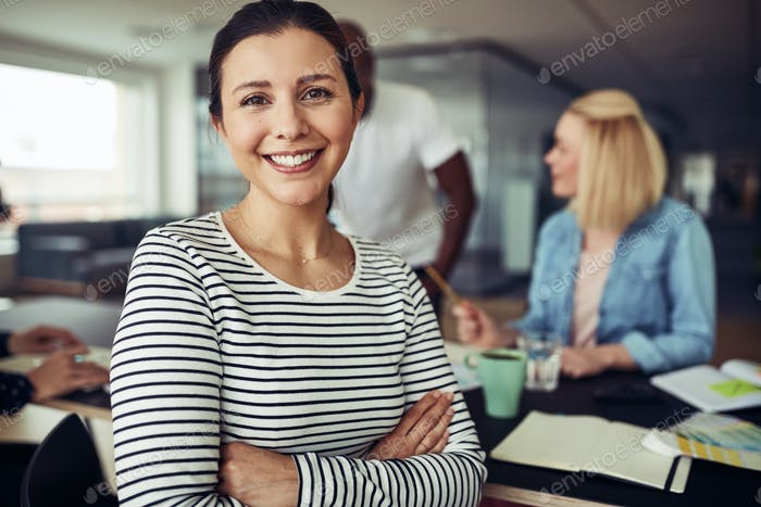 Young businesswoman smiling while sitting with colleagues in an office