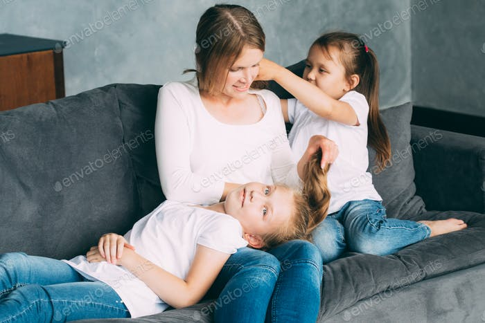 Family together happy. Mother with two daughters home relaxing playing. Family portrait.