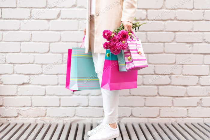 Stylish girl in white clothes holding pink shopping bags. Sale, discount, black friday concept