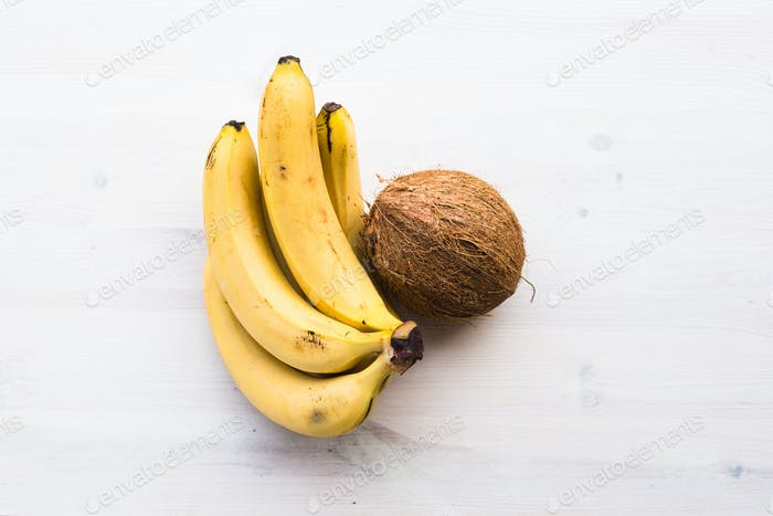coconut and bananas on the wood background