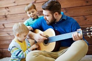 Playing guitar with father photo by Pressmaster on Envato