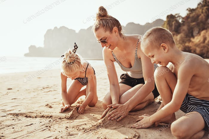 Mother and children playing on a sandy beach during vacation
