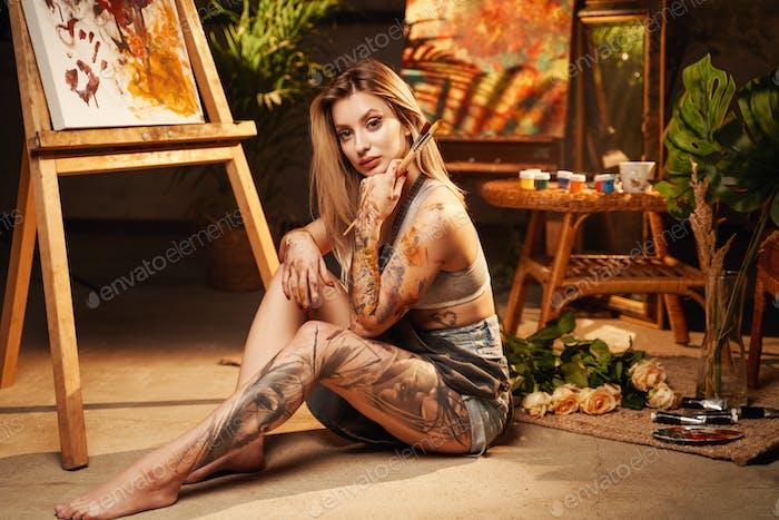 Веселая художница сидит на полу и держит кисти в студии
