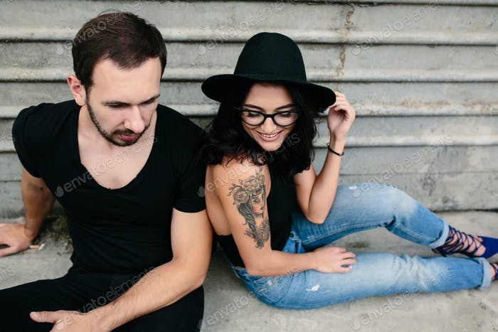 man and woman posing on a background gray wall