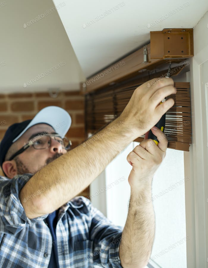 People installing window curtain