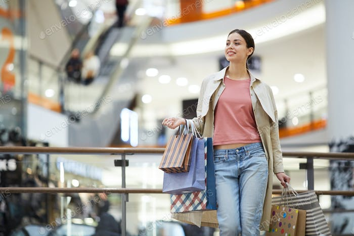 Content woman searching for sale in mall
