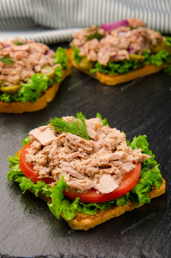 Tuna sandwiches with lettuce tomatoes pickles and onions on slate