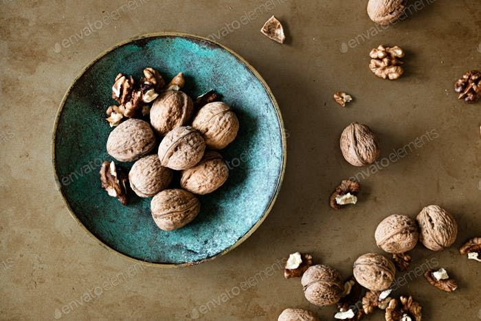 Walnuts in a bowl on a table, overhead view