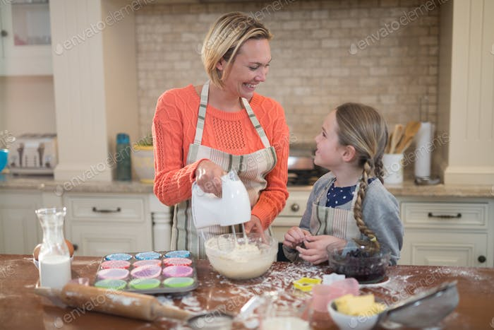 Mother and daughter preparing cup cake in kitchen