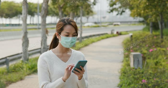Woman wears face mask and uses mobile phone