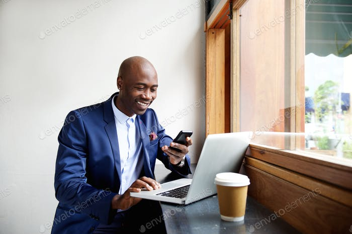 Happy african businessman using phone at cafe