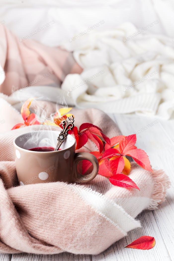 Eine Tasse gesunder Tee in gelben roten Blättern mit beigem Schal auf weißem Holzhintergrund, Kopierraum