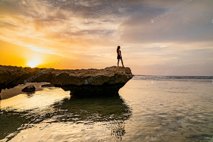 Beautiful girl in dress on the rocky beach at sunset. Red sea