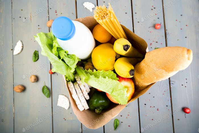 Grocery shopping concept. Different food in paper bag on wooden background.  Top view.