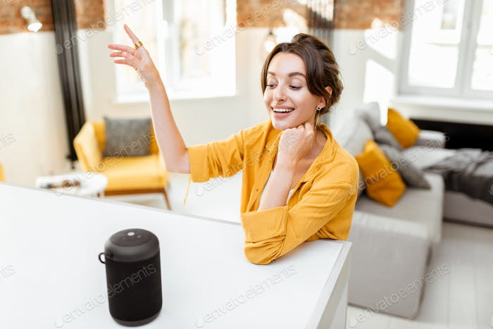 Woman controlling smart home devices with a voice commands