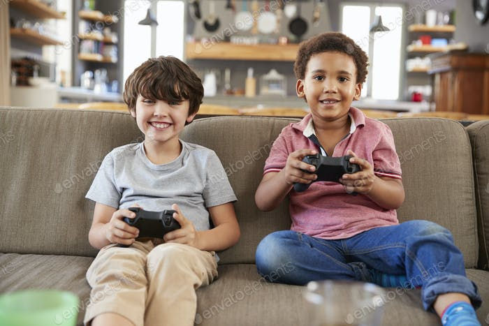 Two Boys Sitting On Sofa In Lounge Playing Video Game Together