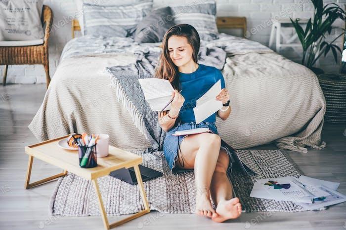 Mädchen mit Notizbuch aus Papier und Diagrammen sitzt auf dem Boden