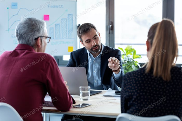 Business people discussing together in conference room during meeting at office.