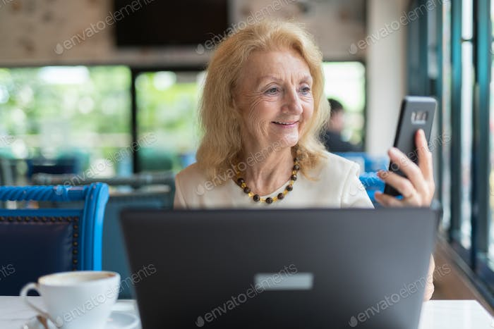 Happy senior woman smiling and while using phone and laptop computer in restaurant
