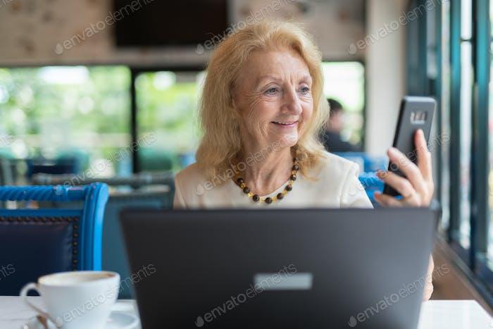 Glückliche Senior Frau lächelnd und während der Verwendung von Telefon und Laptop-Computer im Restaurant
