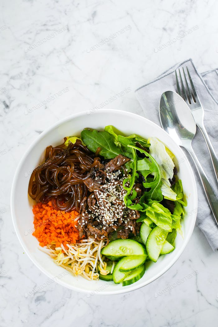 Asian lunch bowl with beef, noodles, mix green leaves and vegetables on marble table