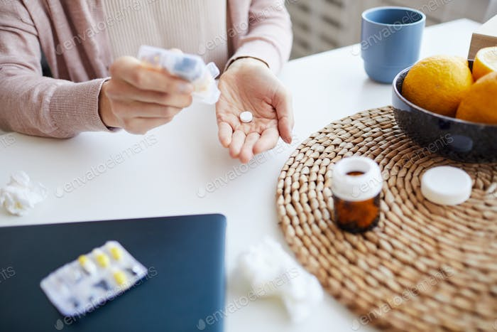 Woman drinking pills from temperature